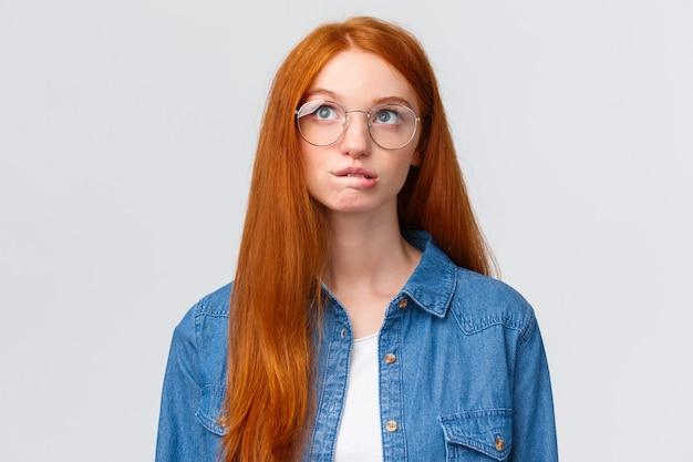 Adolescente ruiva pensativa e curiosa, morder o lábio e olhando para cima como planejar algo