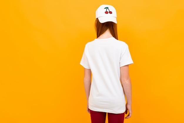 Adolescente ruivo fica de costas em um amarelo isolado