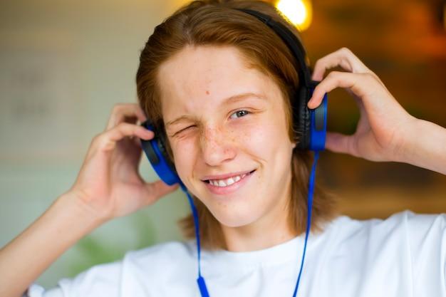 Adolescente ruivo usando fones de ouvido azuis, ele ouve música e sorri