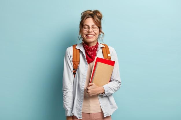 Adolescente satisfeita ri com alegria, mantém os olhos fechados, ouve uma piada engraçada durante o intervalo entre as aulas