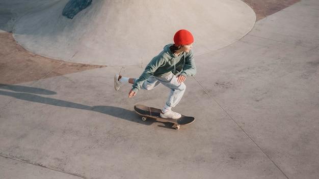 Adolescente se divertindo no skatepark com skate