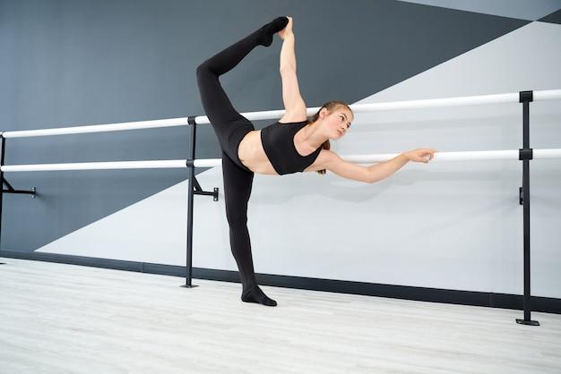 Adolescente se espreguiçando em uma sala de balé