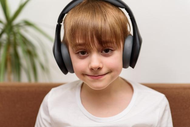 Adolescente se senta em fones de ouvido e sorri. cara ouve música.