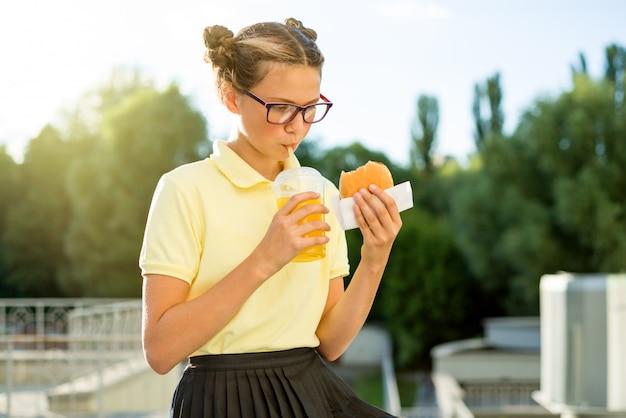 Adolescente, segurando o hambúrguer e suco de laranja