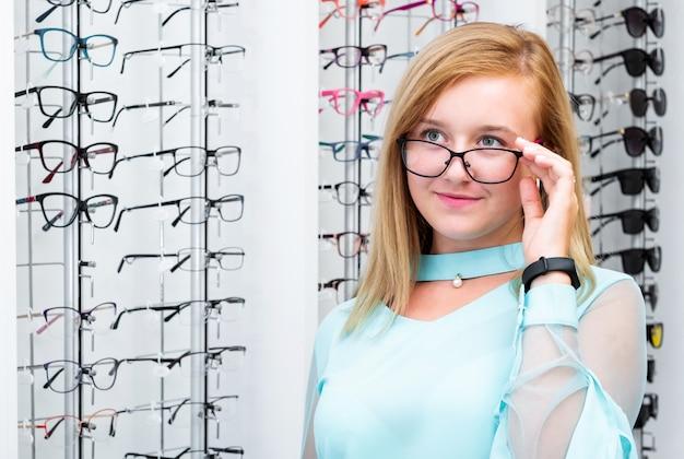 Adolescente, segurando os óculos rosa-preto