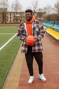 Adolescente segurando uma bola de basquete ao ar livre