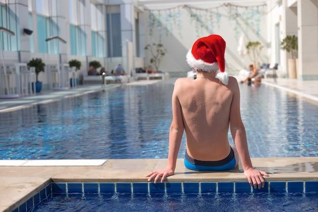 Adolescente sem rosto com chapéu de papai noel vermelho sentado na beira da piscina em um dia ensolarado