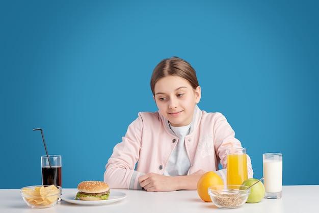 Adolescente sentada à mesa e olhando para um hambúrguer prejudicial à saúde e refrigerante enquanto enfrenta a difícil escolha de nutrição