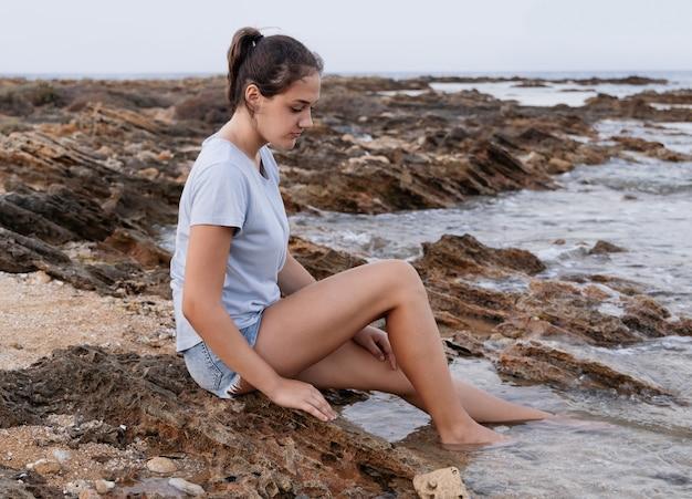 Adolescente sentada na falésia à beira-mar com as pernas na água ao pôr do sol e olhando para baixo, vestindo camiseta azul e shorts jeans, vista lateral. maquete de camiseta