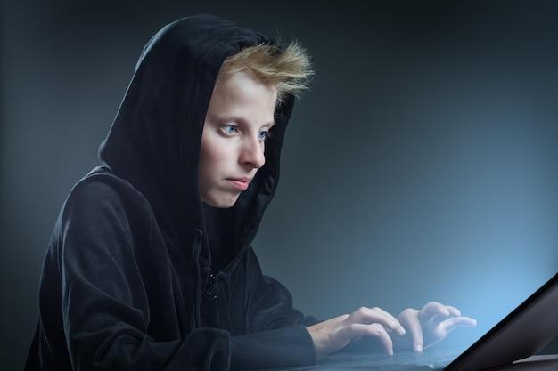 Adolescente sentado atrás de um computador