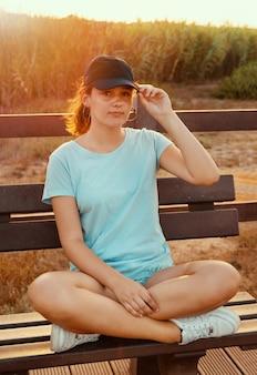 Adolescente sentado de pernas cruzadas em um banco de madeira perto do campo ao pôr do sol, vestindo camiseta azul, boné de beisebol e segurando o visor. maquete de boné e camiseta