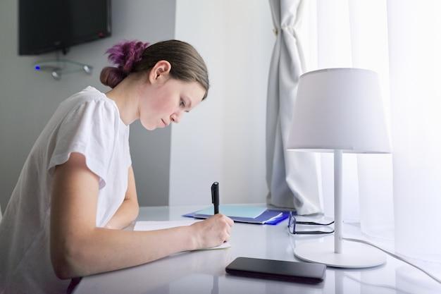 Adolescente sentado em casa na mesa perto da janela e escrevendo no caderno