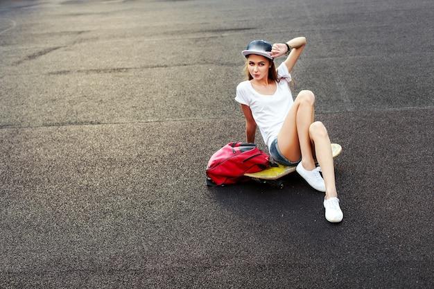 Adolescente sentado no skate com uma mão tocando seu boné