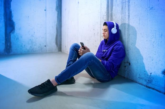 Adolescente sentado ouvindo música no chão