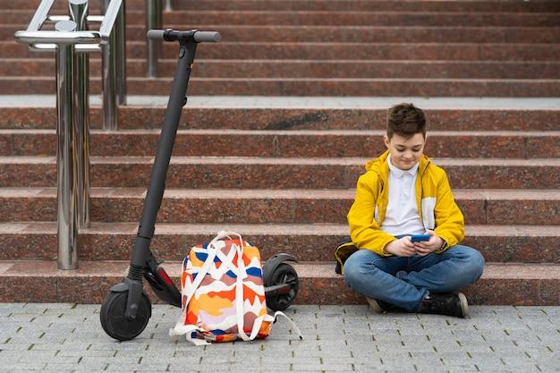 Adolescente sentado perto de sua scooter elétrica e enviando mensagens de texto no smartphone