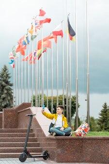 Adolescente sentado perto do prédio da administração