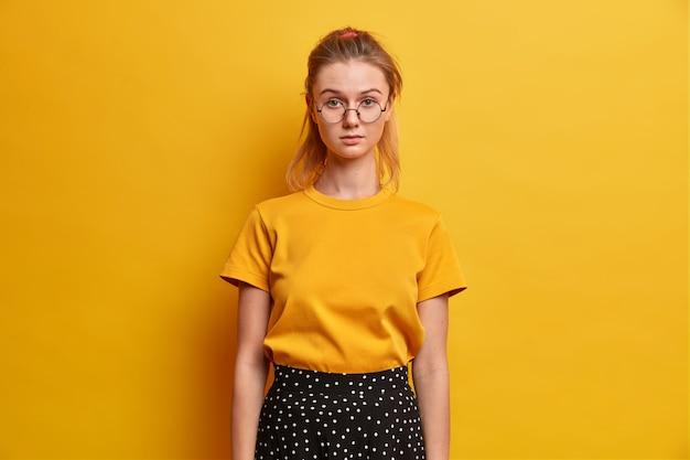 Adolescente séria com rabo de cavalo olha direto tem olhar atento usa óculos redondos, camiseta e saia isolada sobre uma parede amarela viva conversa com os pais