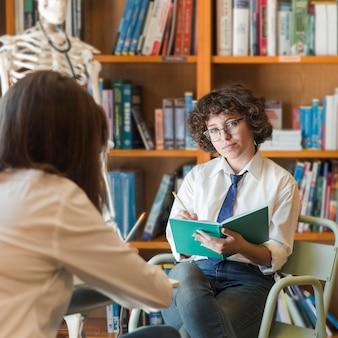 Adolescente sério fazendo lição de casa na biblioteca