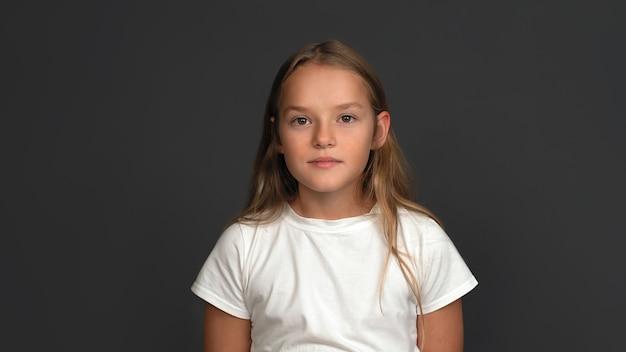 Adolescente sério, garota de 10-12 anos posando