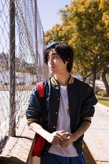 Adolescente sério, olhando para longe através da cerca na rua