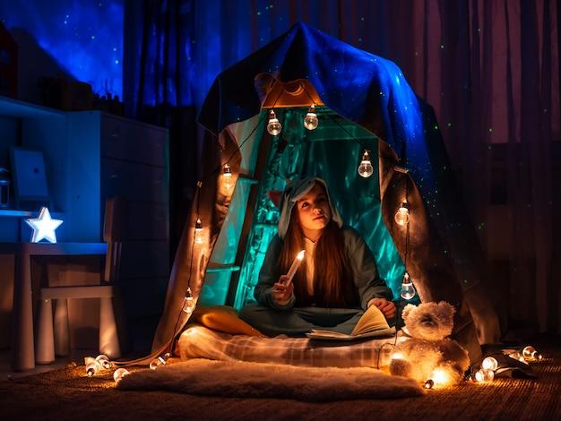 Adolescente sob a forma do anime que senta-se na barraca da home do jogo. cenário com iluminação de festão fantástica