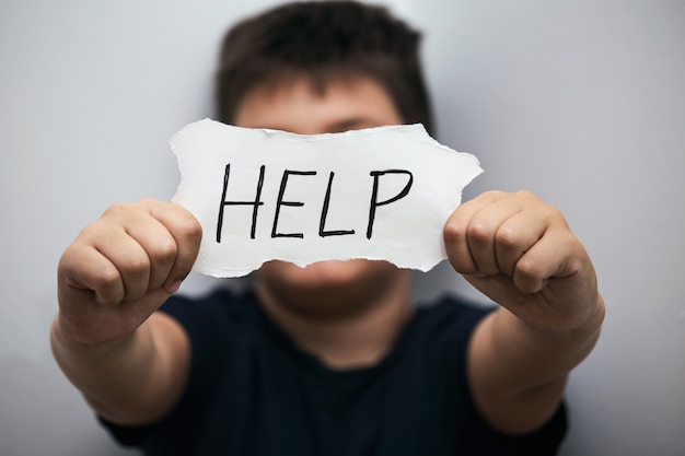 Adolescente solitário deprimida expressão e mostrando um papel com um texto de ajuda.