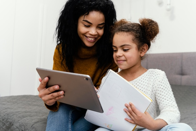 Adolescente sorridente ajudando a irmã usando tablet para escola online