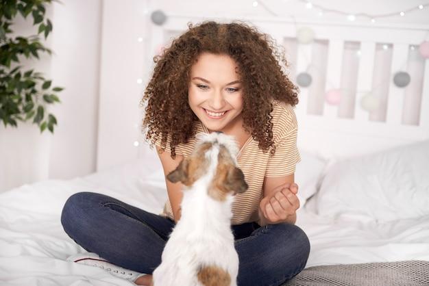 Adolescente sorridente brincando com seu cachorro no quarto