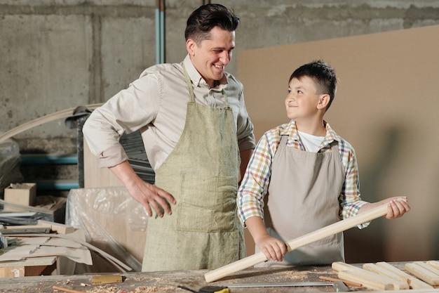 Adolescente sorridente com avental em pé com uma prancha de madeira polida desfrutando do trabalho de carpintaria com o pai
