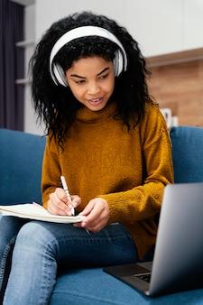 Adolescente sorridente com fones de ouvido e laptop durante a escola online