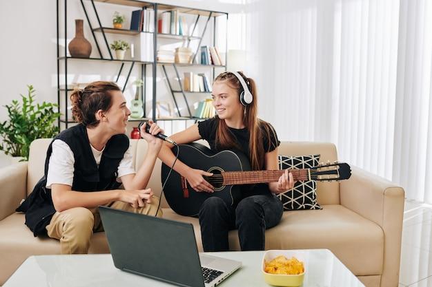 Adolescente sorridente com fones de ouvido tocando guitarra enquanto sua amiga cantando uma música no microfone