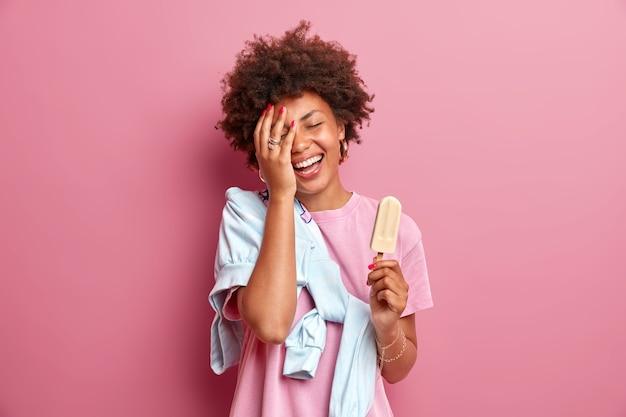 Adolescente sorridente deixa o rosto da palma da mão feliz usa camiseta casual com jumper, aproveita o horário de verão, come delicioso sorvete no palito, tem bom humor isolado sobre a parede rosa. diversão e doces