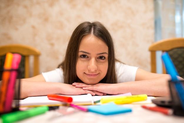 Adolescente sorridente encostada na mesa cheia de lápis, livros e papéis