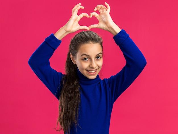 Adolescente sorridente fazendo sinal de coração fazendo sinal de coração acima da cabeça, isolado na parede rosa