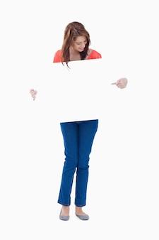 Adolescente sorridente segurando um cartaz em branco ao apontar para ele