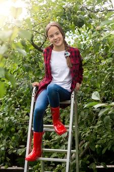 Adolescente sorridente usando gumboots vermelhos posando na escada no jardim de maçãs