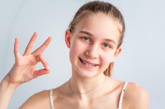 Adolescente sorrindo em suportes ortodônticos, mostrando sinal de ok. menina com aparelho nos dentes. tratamento ortodôntico.
