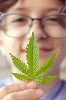 Adolescente sorrindo segurando folhas de maconha na mão