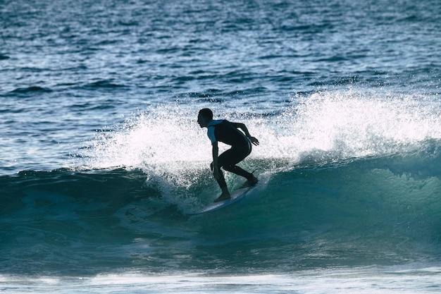 Adolescente surfando na onda em tenerife playa de las americas - wetsuits branco e preto e onda bonita e pequena