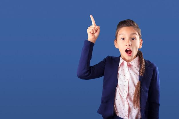 Adolescente surpreendida apontando o dedo para cima no azul clássico