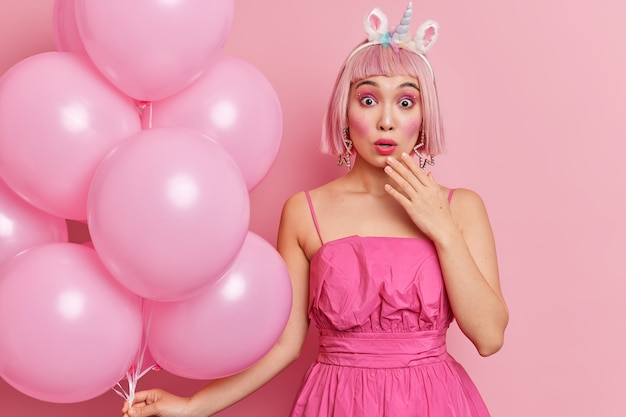 Adolescente surpresa com cabelo rosa olhando chocada para a câmera