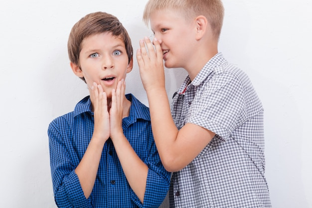 Adolescente sussurrando no ouvido um segredo para um amigo em fundo branco