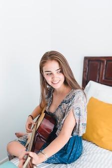 Adolescente talentoso tocando violão no quarto