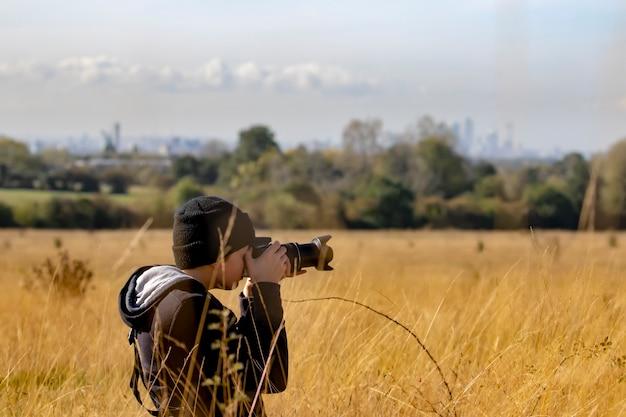 Adolescente tirando fotos com câmera dslr em uma reserva natural