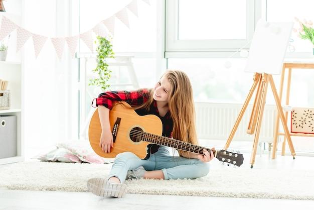 Adolescente tocando violão sentada no chão em uma sala iluminada