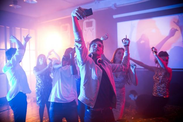 Adolescente tomando selfie na pista de dança