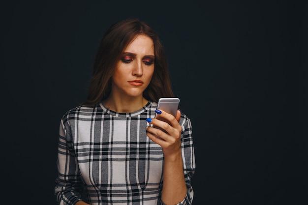 Adolescente triste sendo vítima de cyber bullying on-line, sentado em um sofá na sala de estar de casa