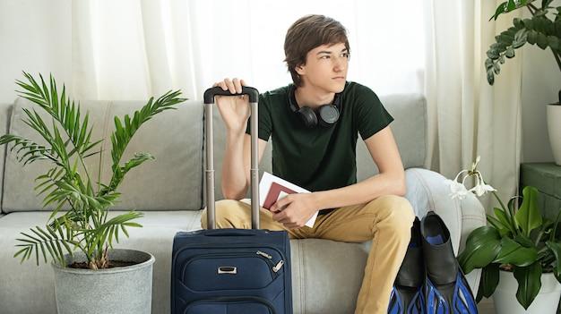 Adolescente triste turista com uma mala e nadadeiras fica em casa