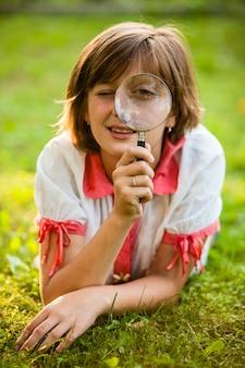 Adolescente usa lupa para descobrir a natureza