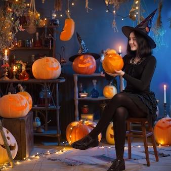 Adolescente vestida de bruxa com abóboras no fundo da decoração de halloween